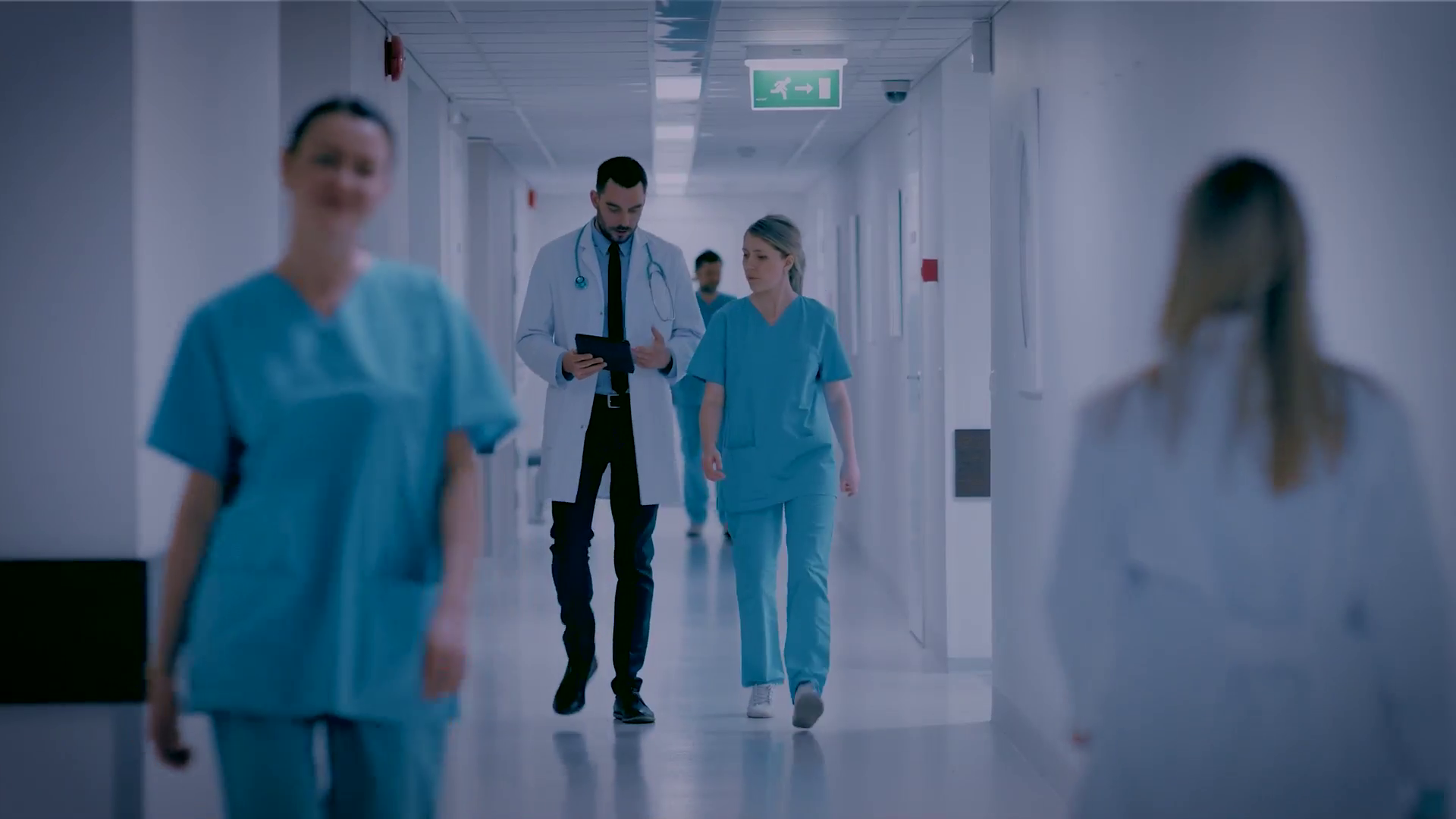 A doctor and a nurse walking through a hospital corridor
